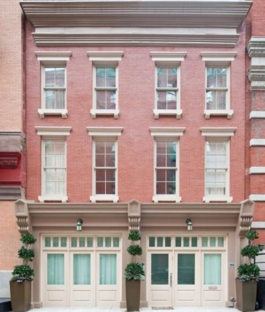 Taylor Swift's home with red walls and double hung glass windows perfectly livens up the white entrance door along with tall plants in containers on each block.