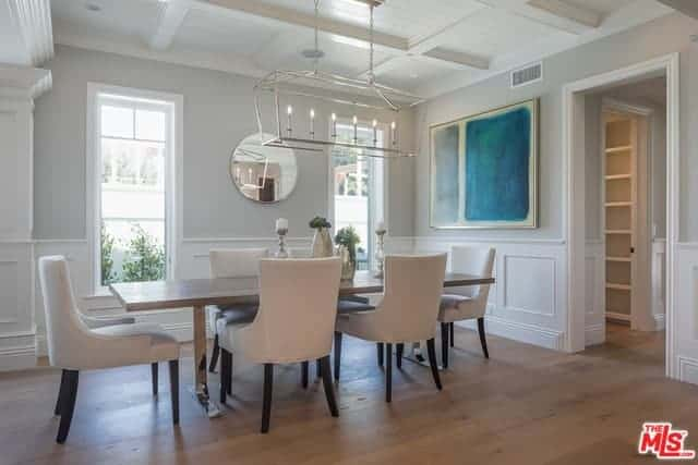 A delightful blue-green painting mounted on the white wall bring a dash of vibrancy to the white brightness of this dining room that has a coffered ceiling and tall windows that light up the wooden table and white dining chairs.