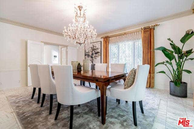 The emphasis of this dining room is the brilliant crystal chandelier that brings forth warm light over the polished wooden table and its white leather dining chairs.