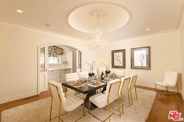 This formal dining room has uniform beige elements on the walls, ceiling and leather cushioned dining chairs as well as the beige area rug over the hardwood flooring. This aesthetic brings the emphasis on the elegant dark wooden table.