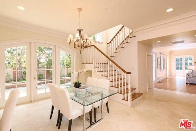 This is a dining area beside the stairs and French glass doors that offer a nice view of the garden outside. The glass-top table is flanked by white leather chairs that are a perfect match for the white-tiled flooring topped with a chandelier.