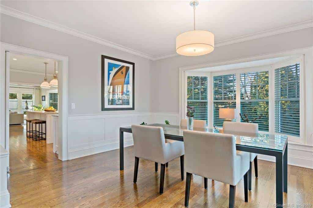 This dining room has a row of windows with colored shutters that stand out against the white wainscoting of the light gray walls that match the cushioned chairs of the glass-top table.
