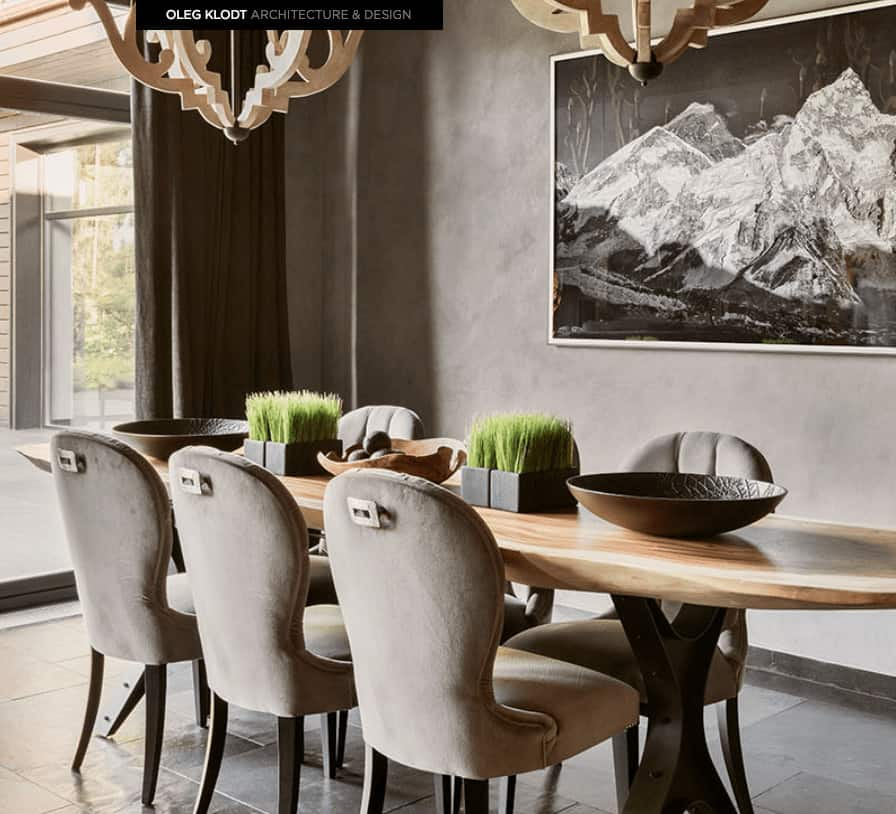The wooden table contrasts the light gray cushioned dining chairs that match the tiled floors and gray walls that is adorned with a majestic Mount Everest painting.