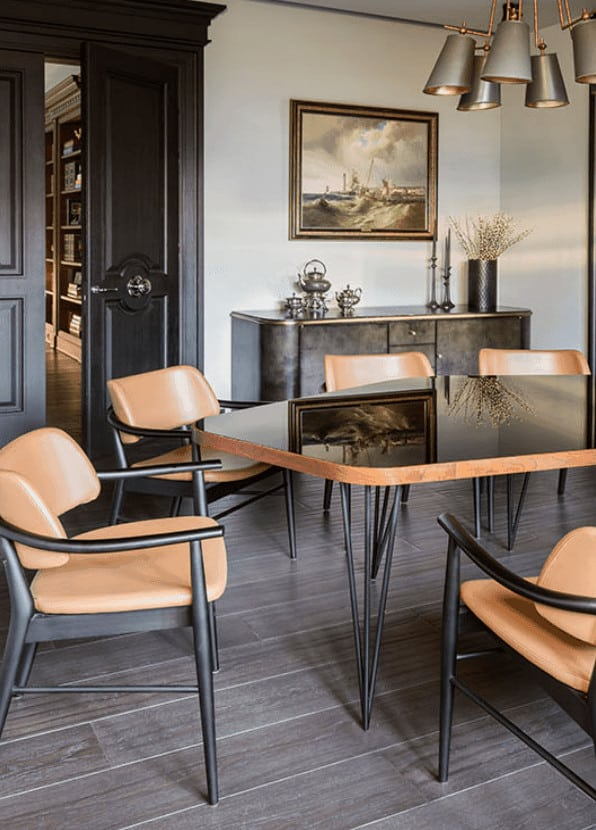 A wonderful painting of the sea mounted on the white wall gazes down on the black-top table with matching leather cushioned chairs with the same dark iron legs. This dining set is a perfect match for the modern chandelier over the table.