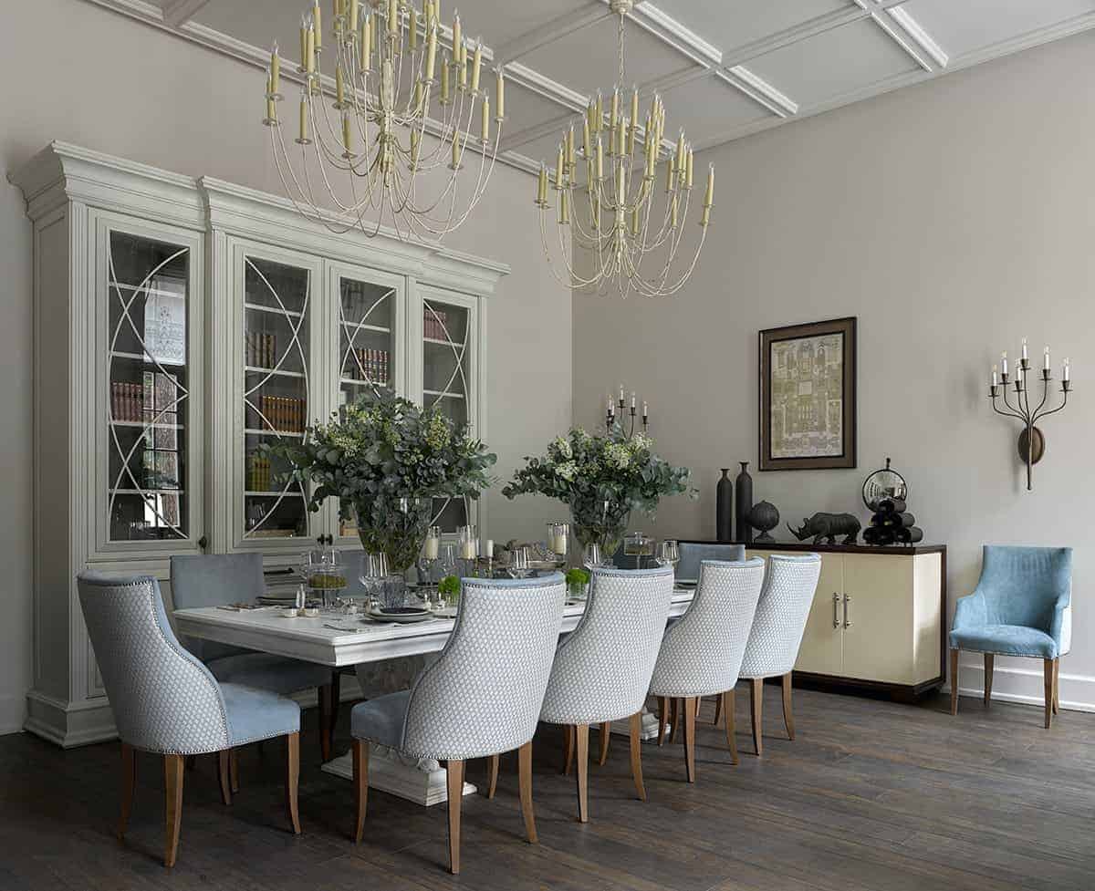 This is an elegant and traditional formal dining room that has hardwood flooring contrasted by the light hues of the cushioned dining chairs surrounding the white dining table that matches the white cabinet by the white wall. The long table is topped with a couple of thin white chandeliers hanging from the white coffered ceiling.