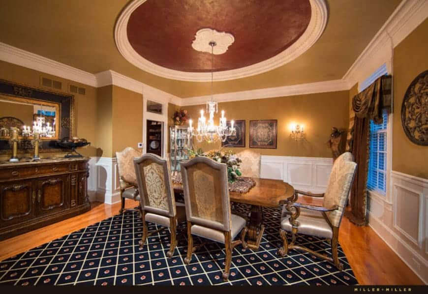 The elegant wooden table is matched with equally elegant wooden chairs that are illuminated by a brilliant white chandelier hanging from the maroon dome of the beige ceiling. This is complemented by a navy blue patterned area rug.