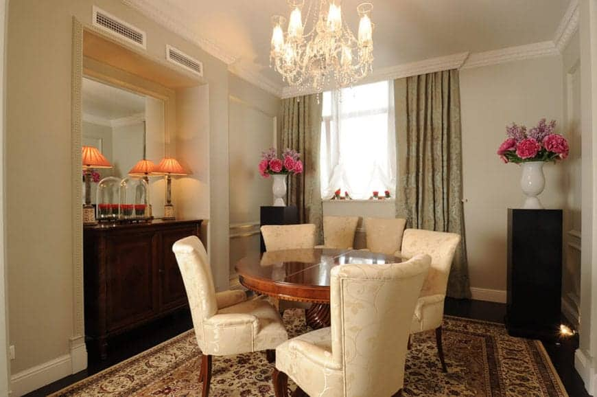 This small dining room has a colorful patterned area rug that makes the beige cushioned dining chairs stand out. These chairs have a subtle floral design that complements the intricate chandelier over the round wooden table.