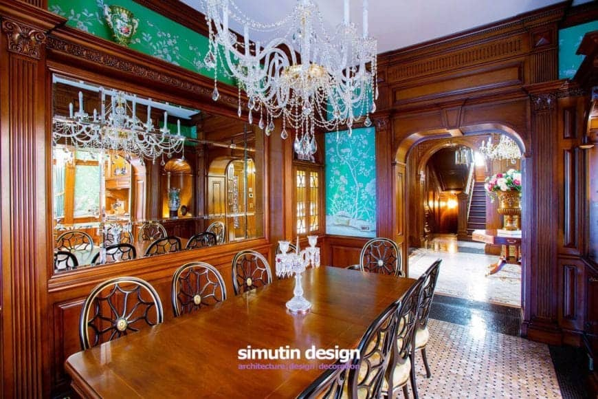 The walls of this formal ding room is dominated by the polished wooden finish reflected by the table and chairs. The spaces in between reveal green floral wallpaper that makes the crystal chandelier stand out.