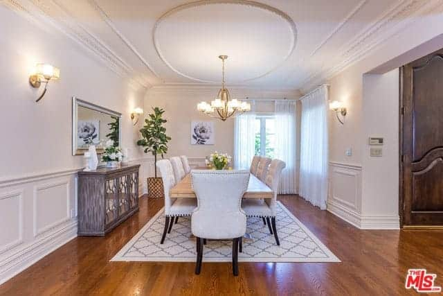 The hardwood flooring is topped with a white patterned area rug that complements the white ceiling and its elegant finish. This is illuminated by the chandelier that matches the wall-mounted lamps on the white walls.