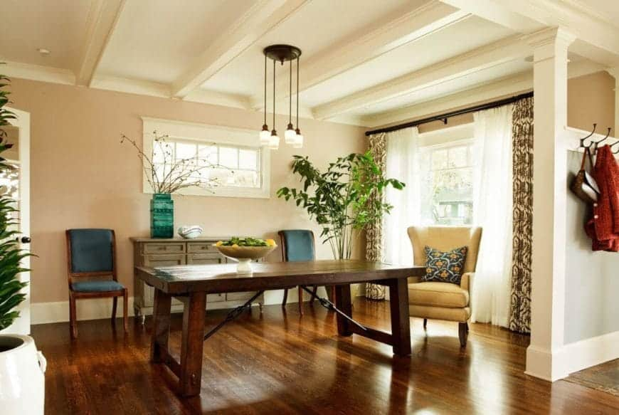This lovely dining room has a heavy dark wooden dining table that perfectly blends in with the hardwood flooring. This contrasts the white ceiling has exposed beams.