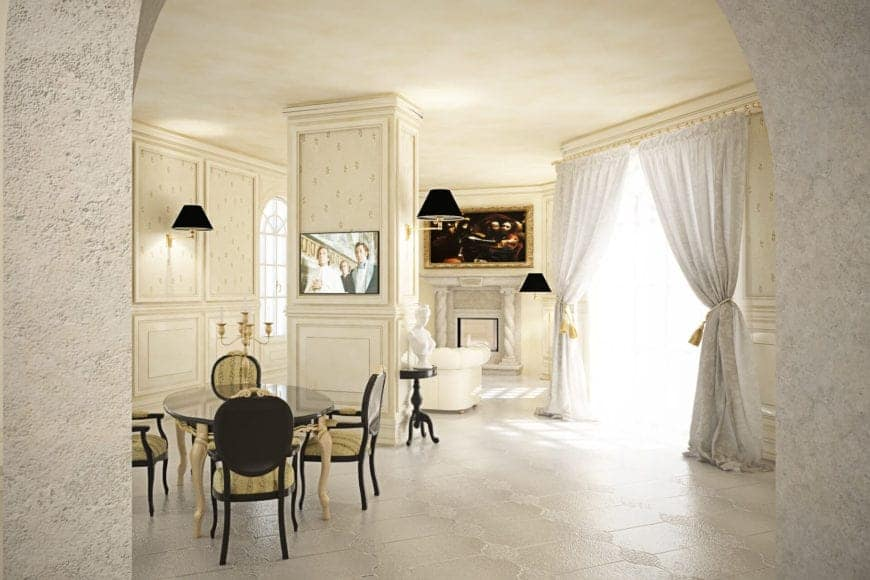 This dining area shares the white great room with the living room area that has the same beige ceiling and white-tiled flooring. The black elements of the round ding table and surrounding oval-backed chairs are a a good contrast to the elegant beige walls and pillar in the middle of the room.