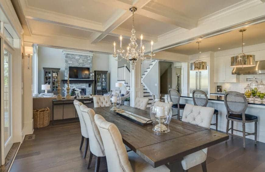 The white coffered ceiling supports a white crystal chandelier that contrasts the dark wooden table and dark hardwood flooring that makes the cushioned dining chairs stand out.