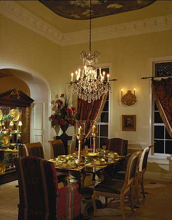 This dining room exudes elegance and luxury with its high beige ceiling that hangs down a majestic chandelier over the dark-top dining table and its dining chairs cushioned with colorful patterns.