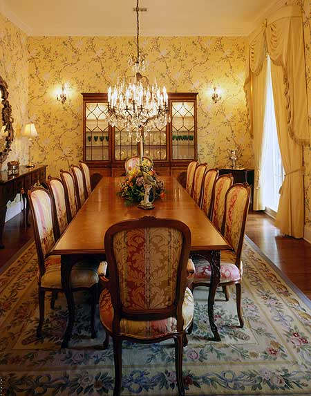 The floral cushions of the chairs surrounding the wooden table match the floral patterns of the colorful floral area rug over the hardwood flooring. This is then complemented by a floral yellow wallpaper on the walls capping off the chic aesthetic.