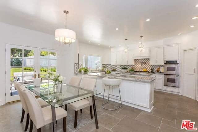This is an informal dining room by the kitchen. It has a glass-top table surrounded by beige cushioned Parsons chairs that fit well with the beige flooring and white ceiling that has a white pendant light over the table.