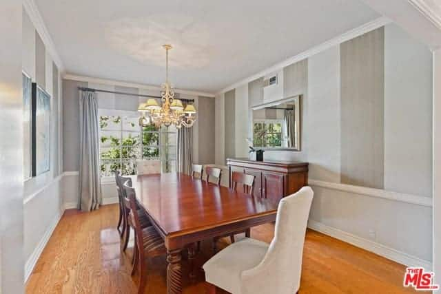 The long redwood table and matching wooden dining chairs blend in with the hardwood flooring while the two cushioned chairs at the opposite ends of the table are white. This is complemented by light gray striped walls.