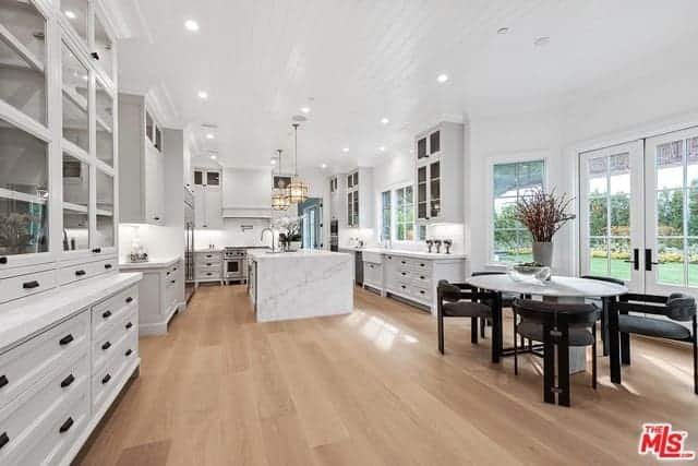 This is an informal dining area beside the huge kitchen with the same hardwood flooring and white shiplap ceiling. It has a modern white round table surrounded by modern armchairs that stand out against the white French glass doors.