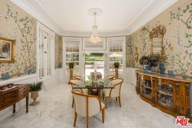 This is a charming formal dining room that has chic floral wallpaper with a salmon pink background that complements the white tray ceiling and white marble flooring. The glass-top dining table is surrounded by beige chairs.