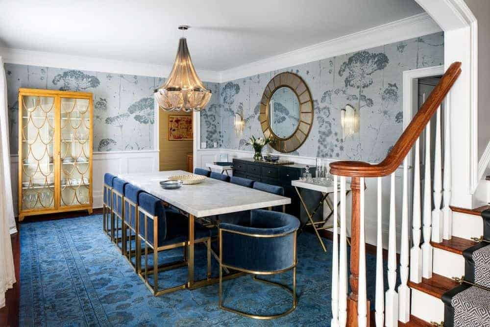 The blue floral patterned area rug covering most of the hardwood flooring matches with the blue velvet chairs surrounding the white marble top table. This floral blue aesthetic is paired with light gray floral wallpaper covering the walls.