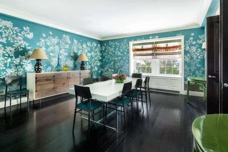 The charming green walls of this formal dining room has floral and tree-like patterns that serve as a nice contrast to the pure white ceiling and dark hardwood flooring. This makes the white-top modern table stand out with its surrounding green chairs.