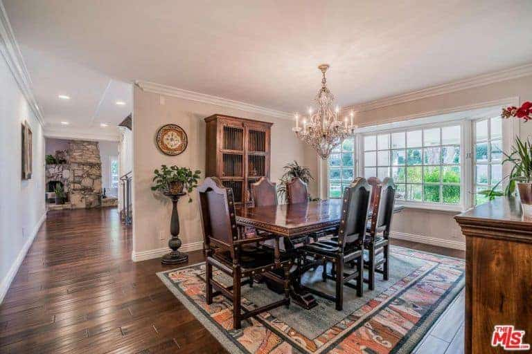 The colorful patterned area rug over the hardwood flooring offers a nice colorful contrast to the dark wood table surrounded by studded wooden chairs that stand out against the salmon pink walls and ceiling.