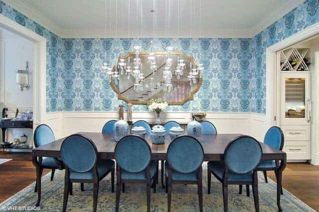 The blue oval-backed chairs surrounding the large wooden table is complemented by the light blue elegantly patterned walls and area rug underneath.