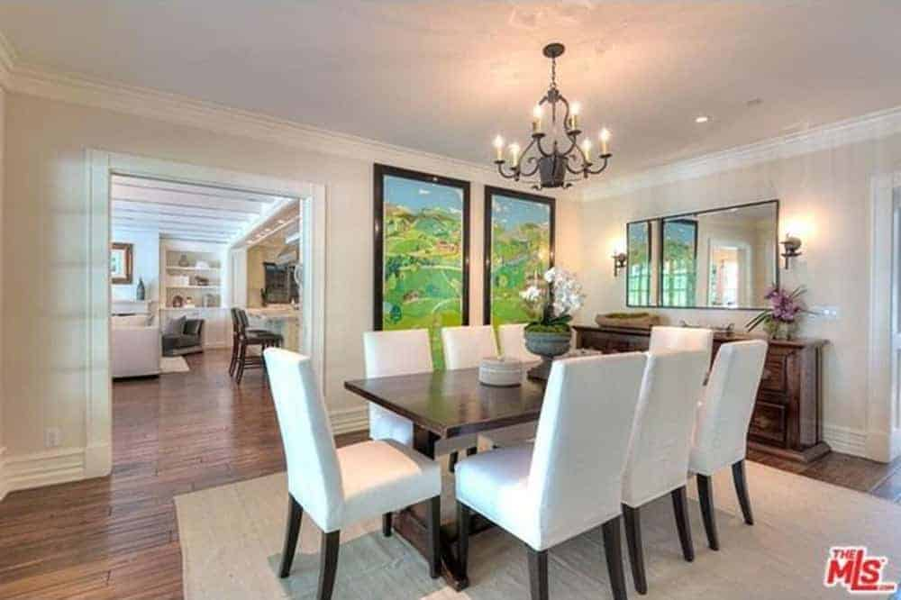 The long wooden table is nicely paired with a wrought iron chandelier that stands out against the white ceiling the same way the table stands out against the white walls and the white cushioned dining chairs over the light gray rug.