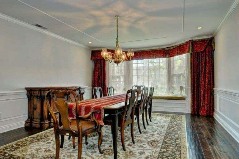 This is a spacious and simple dining room with a long wooden table surrounded by wooden chairs that pair nicely with the hardwood flooring covered by a green patterned area rug. The highlight of this dining room is the elegant chandelier.