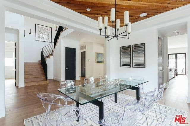 The glass-top dining table is paired with see-through plastic modern chairs over a patterned white area rug that matches the white tray ceiling and its modern chandelier.