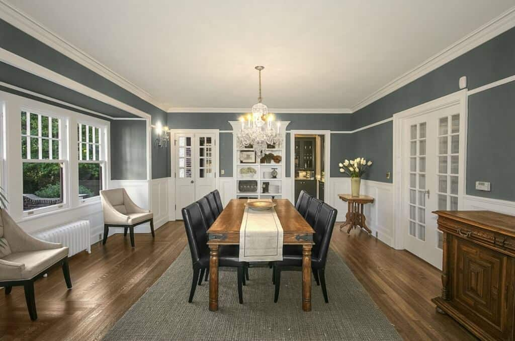 This is a spacious dining room with a large white ceiling that contrasts the hardwood flooring and the dark gray rug underneath the wooden table and its black leather chairs.