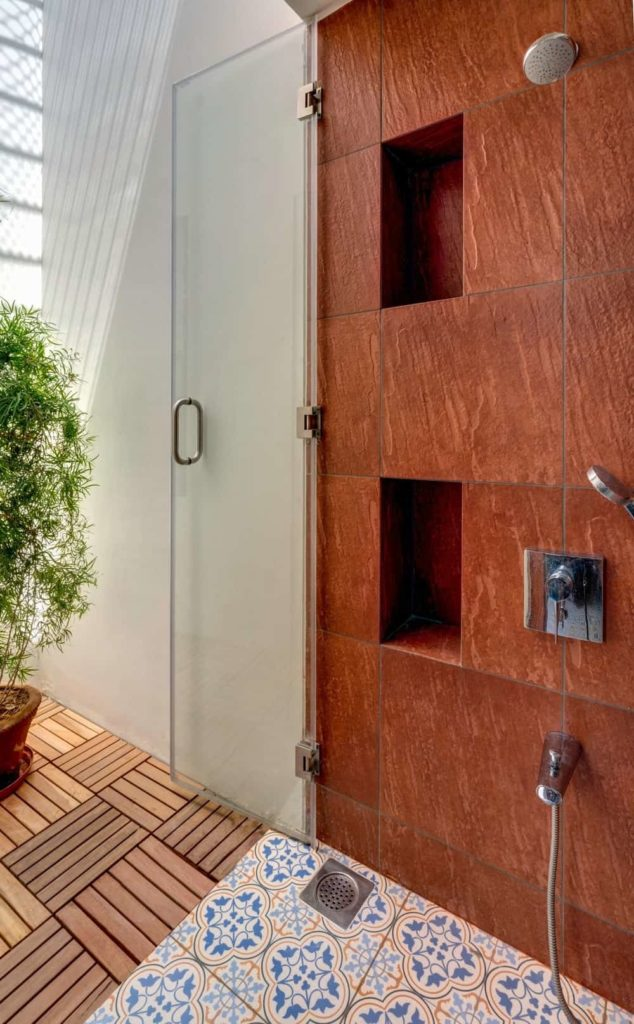 This Tropical-style bathroom has a shower area with a glass door leading to an outdoor area with a potted plant and wooden slat flooring that are all illuminated by the sunlight coming in. This serves as a nice background for the shower area that has earthy red textured tiles on its wall and blue patterned tiles on the flooring.
