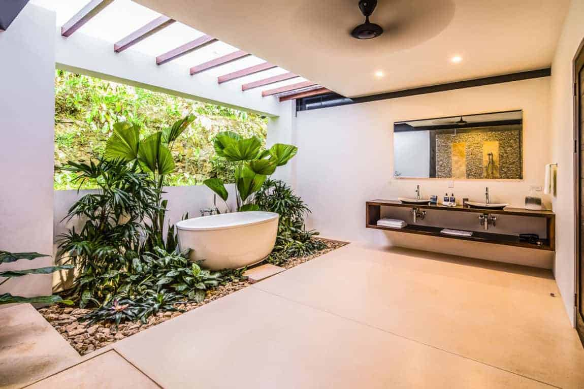 This gorgeous Tropical-style bathroom has a miniature tropical garden surrounding the freestanding bathtub with its area illuminated by natural lights cascading from the skylights above and the wide window behind it. This is paired with a wooden floating vanity with two simple sinks.