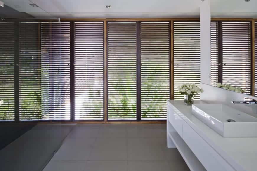 This Tropical bathroom has a relaxing and zen aura to its simple black glass-enclosed shower area that is contrasted by the white vanity across from it. These are balanced by the gray flooring tiles as well as the shuttered tall windows with glimpses of the tropical trees outside.