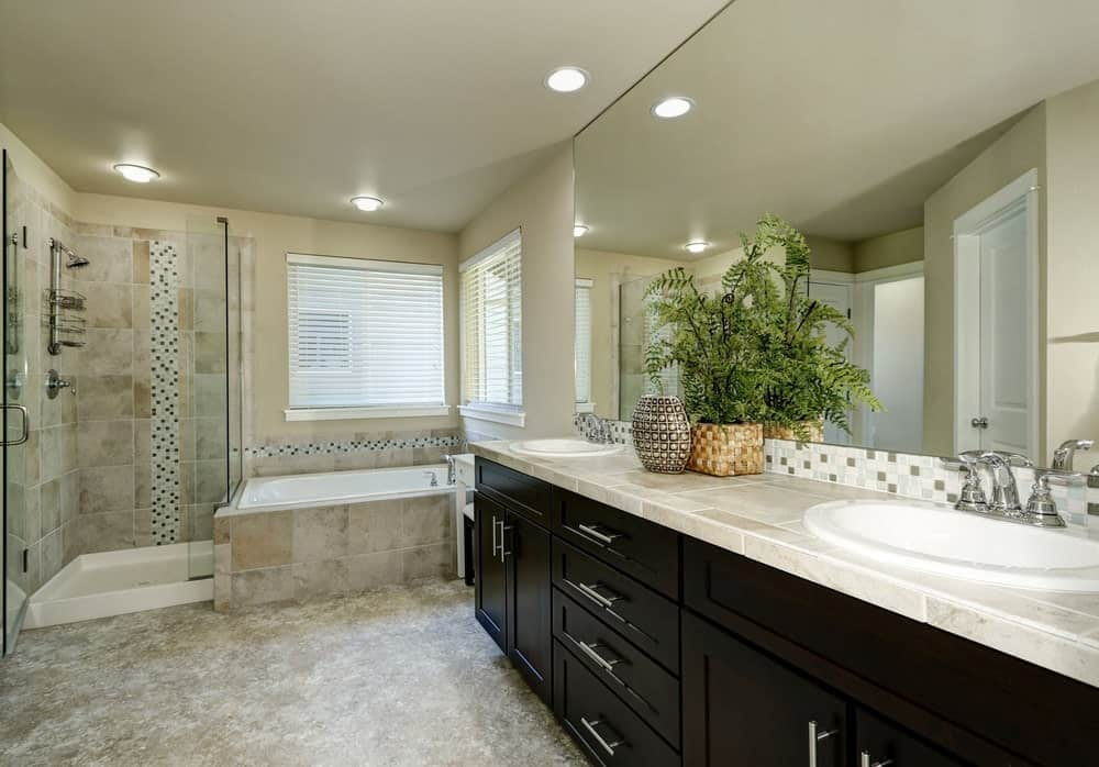 The beige marble flooring matches those on the walls of the glass-enclosed shower area as well as the housing of the bathtub on the corner. This is contrasted by the dark wooden cabinets and drawers of the vanity that has a large mirror adorned with a fern in the middle.