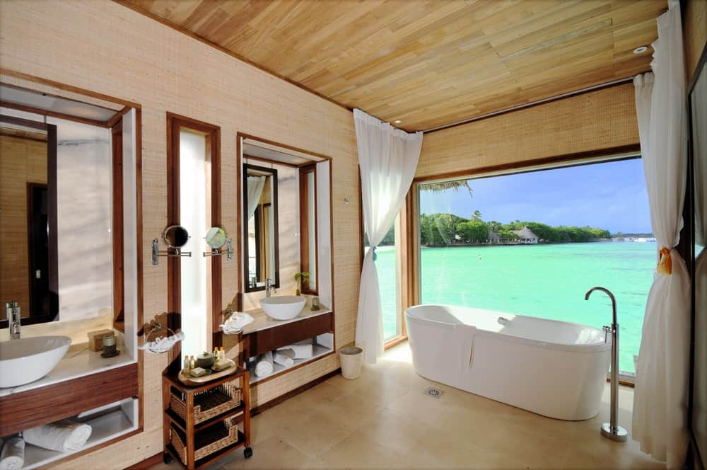 The highlight of this Tropical-style bathroom is the gorgeous view of the sea right outside the large glass window by the freestanding bathtub that is complemented by the beige flooring tiles as well as the beige walls and wooden ceiling.