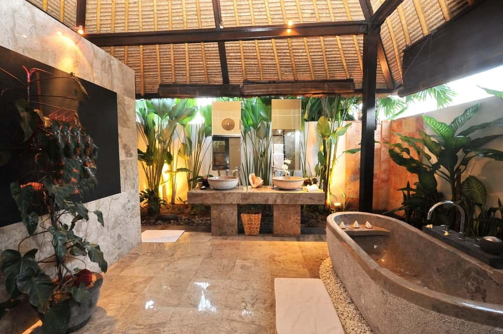 The large stone bathtub matches the stone structure of the two-sink vanity on the far wall. These are surrounded by stone walls that are accented by tropical plants placed by the wall and lit with yellow lights matching those mounted on the wooden arched ceiling.