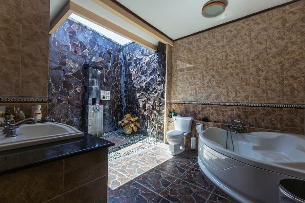 There is a large bathtub beside the toilet that stands out against the brown marble walls and patterned flooring tiles. The highlight of this bathroom is the outdoor shower area surrounded by tall textured stone walls that is augmented by the natural lights.