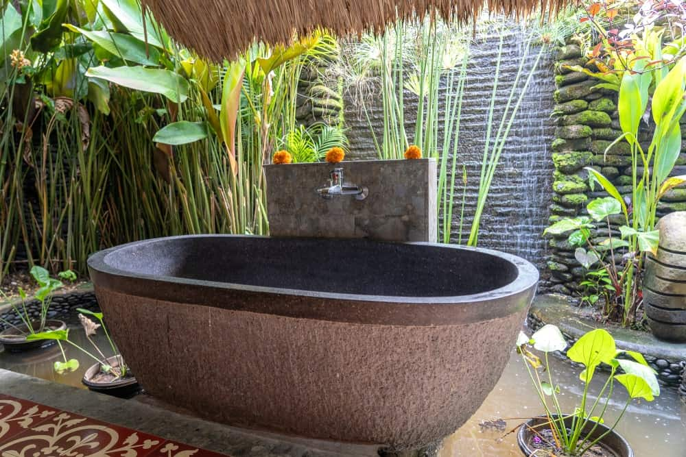 This Tropical-style bathroom has an outdoor bathing experience with its gray stone bathtub that is surrounded by tropical plants and within a lush tropical landscape of stone and potted plants with the sound of trickling water in the background.