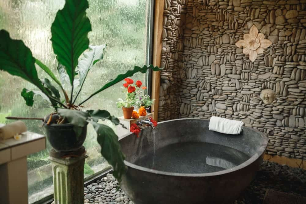 The round stone bathtub of this Tropical-style bathroom pairs well with the pebbled flooring as well as the wall behind it that is made of various stones and adorned with flower artwork. These are all illuminated by the tall glass window that is blurred by running water for privacy.