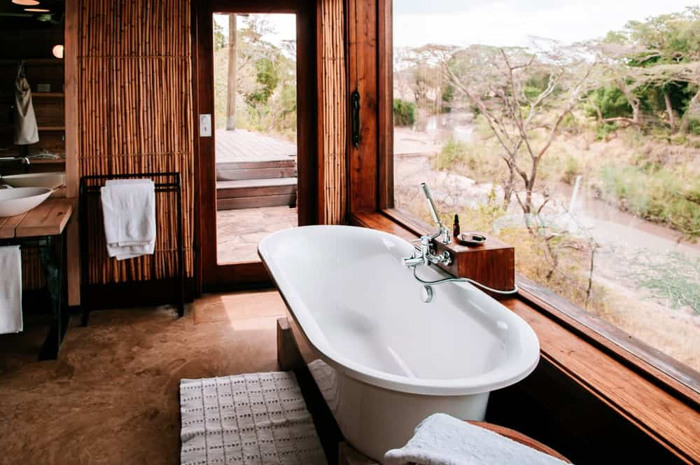 The natural lights coming in from the large glass window makes the freestanding bathtub shine. This is contrasted by the brown marble flooring and the wooden bamboo walls and wooden vanity. There is a beautiful view of the riverside scene that complements the simple tones of the bathroom.