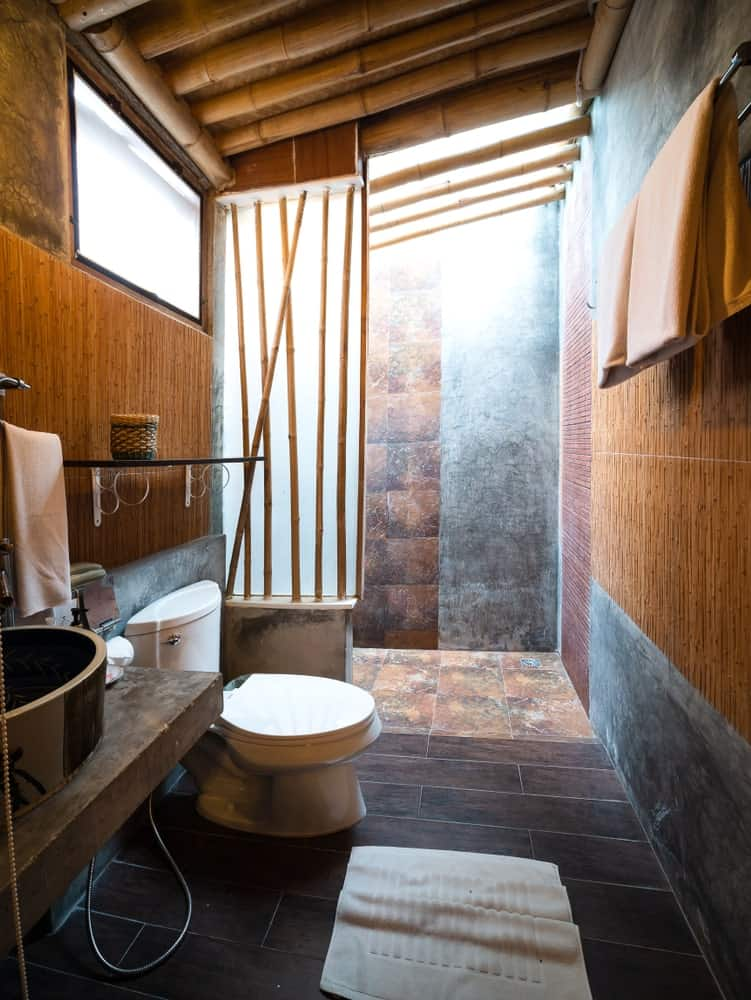 This charming Tropical-style bathroom is dominated by the various bamboo materials used. The wooden ceiling is supported by thick bamboo while the walls are adorned with thin strips of bamboo. The frosted glass wall of the shower area is also framed with bamboo.