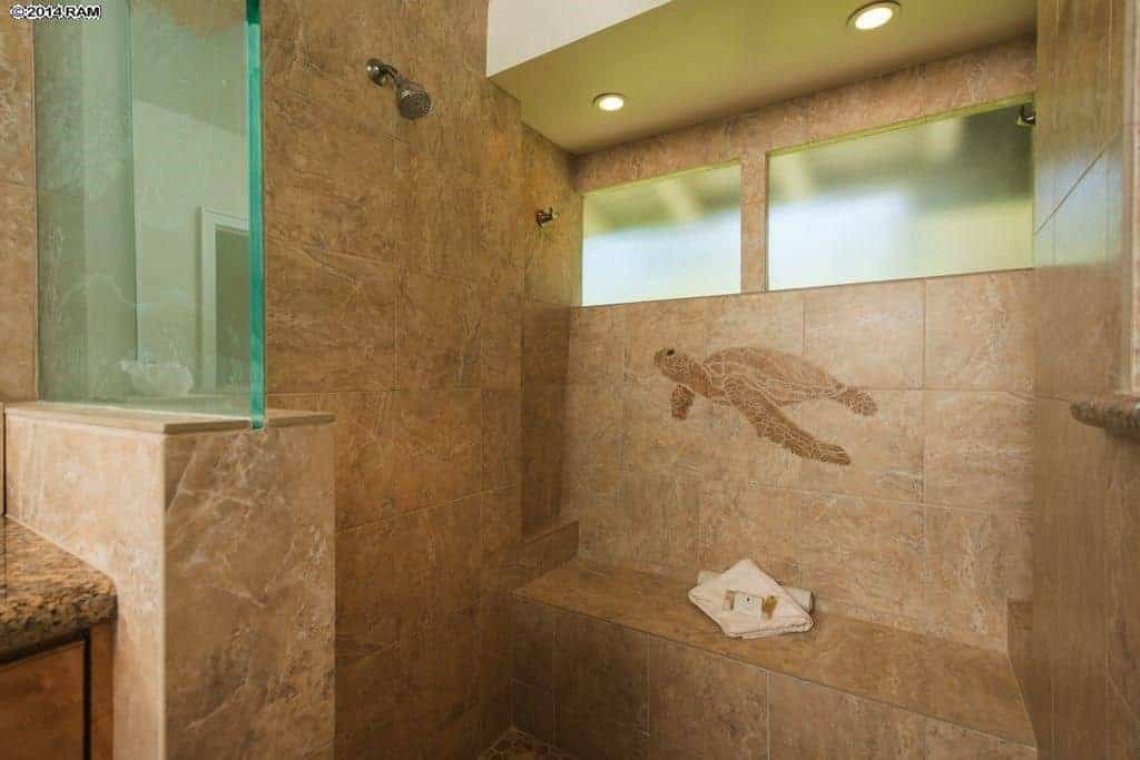 The gorgeous brown marble tiles of this Tropical-style bathroom is brightened by the recessed lights of the beige ceiling as well as the natural lights of the frosted glass window. This wall in the shower area is adorned with a charming depiction of a turtle.