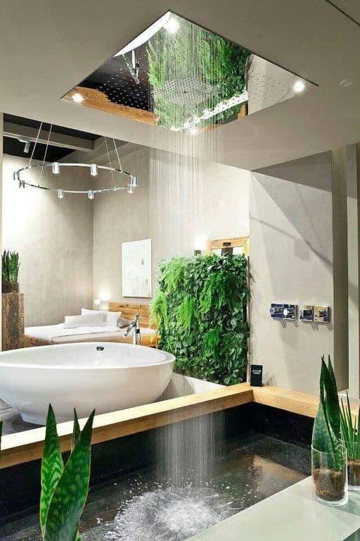 This charming Tropical-style bathroom is right beside the bedroom without any walls. It has an overhead shower that seems like rain in its shower area that is adorned with aloe plants. Beside this is the white freestanding bathtub accented with a hedge of plants beside it.