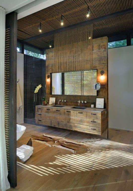 This is a Tropical-style bathroom with hardwood flooring that blends with the wooden structure of the two-sink vanity that also houses the wide mirror that is flanked by wall-mounted lamps adorned with the same materials as the ceiling.