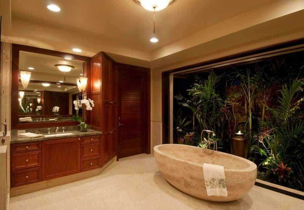 The beige marble freestanding bathtub blends with the beige flooring that is augmented by the yellow lights coming from the recessed lights and flush-mount light of the beige ceiling. These are given a nice background of tropical plants right outside the glass window of the bathtub.
