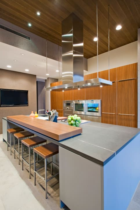 This is a perfect example of a modern kitchen that's not sterile or cold. The lines and materials are modern in every way, yet the liberal use of a medium tone wood gives the space a nice warmth.