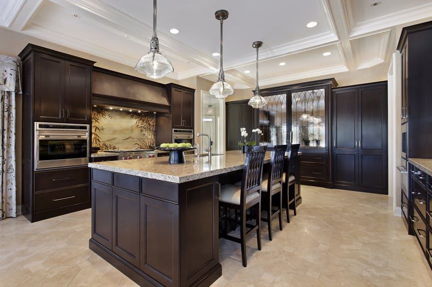 The chocolate brown custom cabinetry is the standout here. The u-shape offers plenty of storage and the large center island creates plenty of counter space. In fact, you'll notice the only real counter space is that offered by the island.