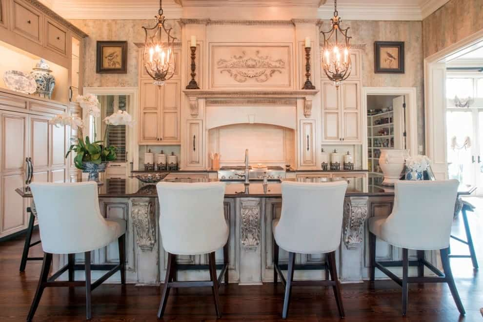 Beige counter chairs sit at a distressed island bar topped with black granite counter. It is accompanied by a pair of pendant lights along with white cabinetry and inset appliances.