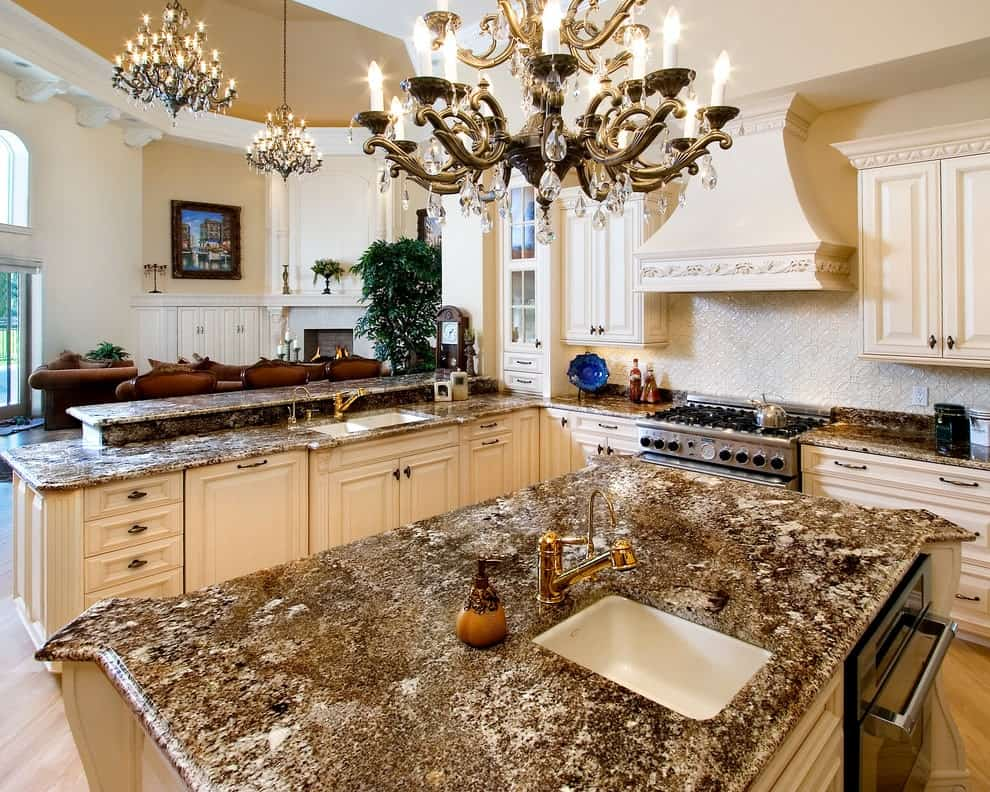 Deluxe kitchen illuminated by a fancy candle chandelier that hung over the granite top island fitted with a porcelain sink and gold fixtures. It has white cabinetry and an ornate range hood fixed above the textured backsplash tiles.