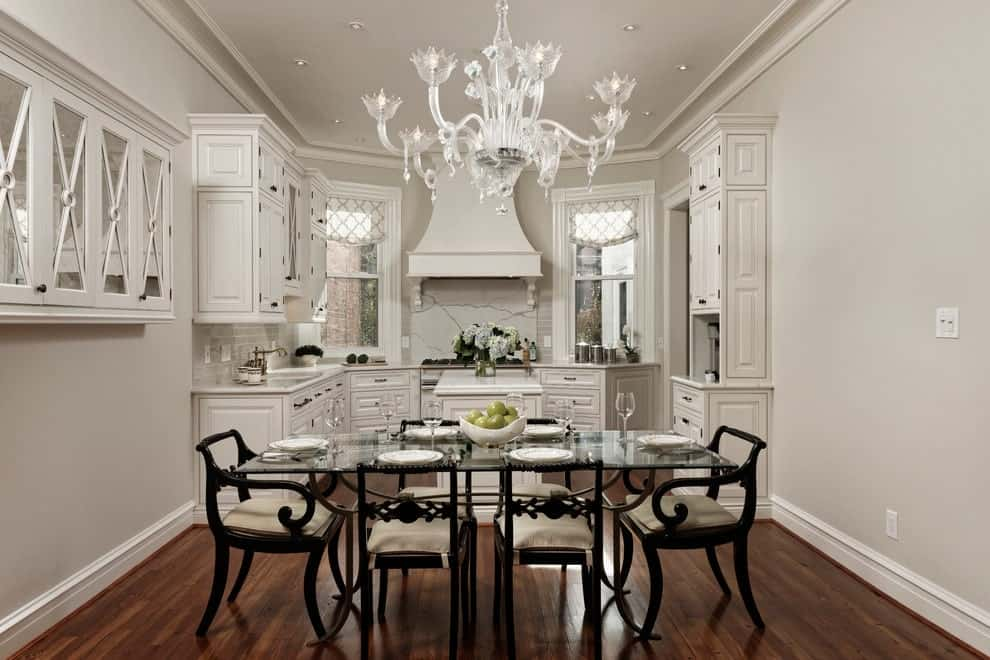 White kitchen with a shared dining space featuring dark wood cushioned chairs and a rectangular dining table lighted by a gorgeous glass chandelier. It has rich hardwood flooring and picture windows dressed in patterned roman shades.